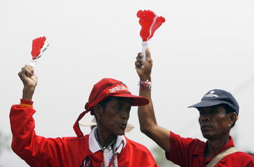 Supporters of former Prime Minister Thaksin Shinawatra use a noise maker during a rally in Bangkok