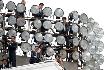 Cameramen take position atop one of buildings in the capital's main ceremonial square during a mass rally and parade, a day after the ruling party wrapped up its first congress in 36 years by elevating him to party chairman, in Pyongyang