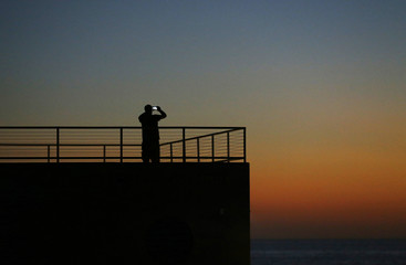 A man takes a picture with his mobile phone after sunset at Moonlight Beach in Encinitas, California