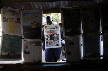 A man displays the front page of a newspaper at a street stand in Bamako