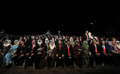 Palestinian couples sit on stage during a mass wedding ceremony in the West Bank city of Jericho
