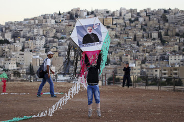 A boy prepares to fly a kite with a portrait of Hamed, a Jordanian prisoner held in an Israeli jail, during a protest in Amman