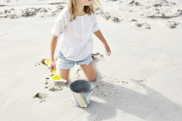 Little girl playing on the beach with bucket and shovel