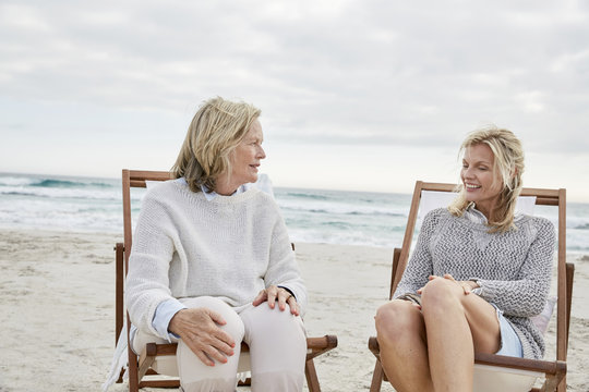 Mother and daughter talking on the beach sitting in deck chairs