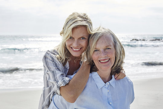 Mother and daughter embracing by the sea