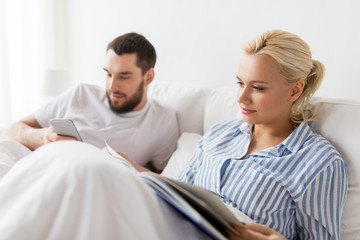 couple with book and smartphone in bed at home