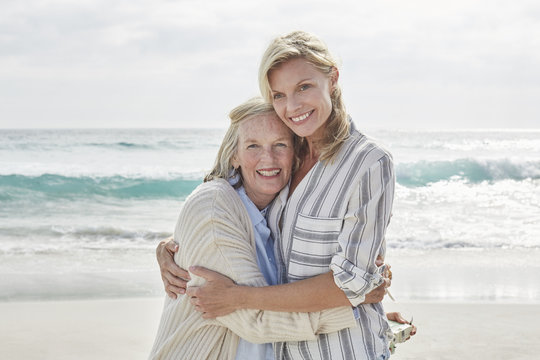 Senior woman and her adult daughter standing on the beach, embracing