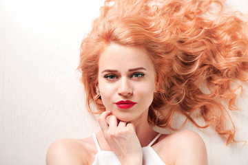 Portrait of young woman with blonde hair on white wooden background