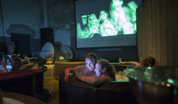 Two movie fans check their cell phone as they enjoy a hot bubble bath while watching a movie at the Hot Tub Movie Club in Amsterdam