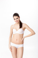 portrait of smiling young brunette woman with perfect sporty body in white underwear  on white background