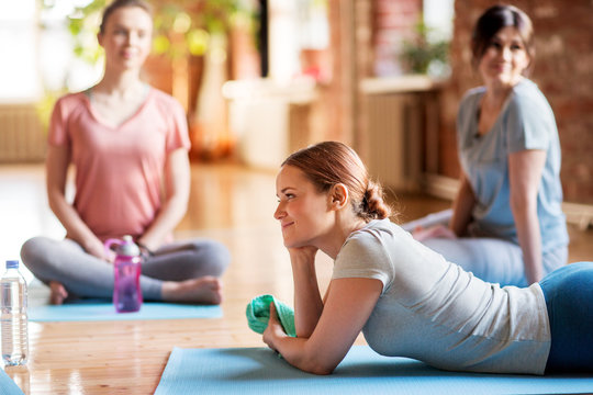 group of women resting on yoga mats at studio