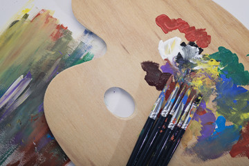 Paint brushes, palette and artwork