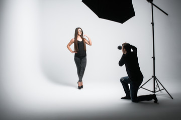 Professional photo shooting at the studio. Beautiful young model is smiling and posing. the photographer is taking pictures with a digital camera