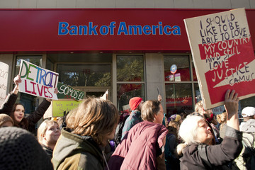 People affiliated with the Occupy Wall Street movement walk past a Bank of America branch during a march to the New York City Supreme Court