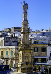 View on the Statue of San Oronzo and the Old Town of Ostuni, Puglia, Italy.