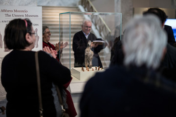 Visitors applaud following a presentation of a 7000-year old Neolithic statuette on temporary display at the National Archaeological Museum in Athens