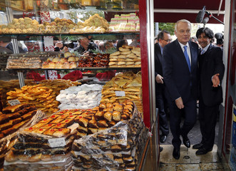 French Prime Minister Jean-Marc Ayrault enters a Tunisian pastry shop during a one day visit in Marseille