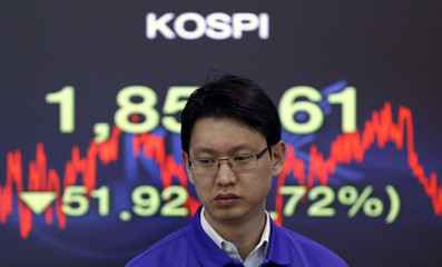 A foreign currency dealer from the Korea Exchange Bank walks past a screen displaying the KOSPI at the bank's dealing room in Seoul