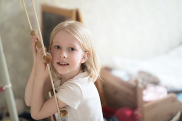 Girl child blond at home on rope ladder