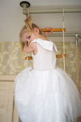 Girl blond in dress at home on rope ladder