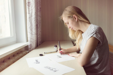 blonde girl writes with a brush and ink, letting