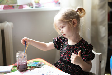 Girl blond child draws watercolor