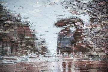 reflet dans une flaque d'eau d'un couple marchant avec un parapluie sur un place pavée