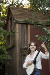 Woman playing banjo outdoors