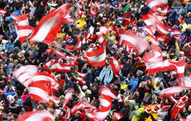 Austrian ski jumping supporters wave national flags during the third event of the 60th four-hills ski jumping tournament in Innsbruck