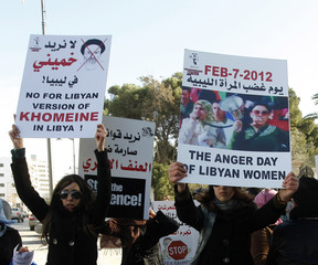 Women hold banners during a demonstration for women's rights in Tripoli