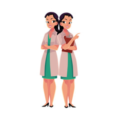 Two female, woman doctors in white medical coats, one with arms folded, another holding clipboard, cartoon vector illustration isolated on white background. Full length portrait of two female doctors