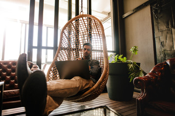 Man relaxing in office lounge with laptop