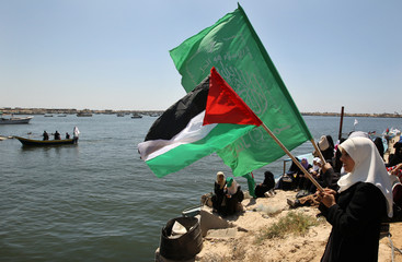 Palestinian women wave Palestinian and Hamas flags during a protest at Gaza's seaport