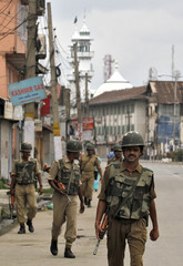 Indian policemen patrol on the seventh consecutive day of a curfew in Srinagar
