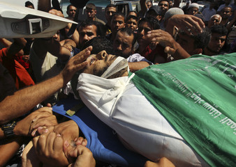 Palestinians carry the body of Hamas militant Hamam Abu Qadus during his funeral in Gaza City