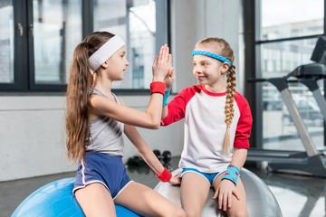 two little girls in sportswear sitting at fitness studio, children sport concept