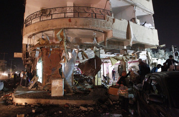 Civilians empty their shops damaged by what activists say was a Scud missile from forces loyal to Syria's President Bashar al-Assad in Raqqa, eastern Syria