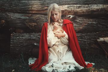 Blond woman hugging little rabbit