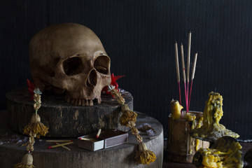 Altar have old skull and candle with incense in former worship / Still life and selective focus.
