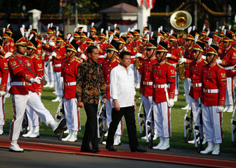 Indonesian President Widodo reviews an honour guard with visiting Philippines President Duterte at the presidential palace in Jakarta
