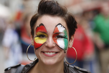 A girl with her face decorated with painte butterfly wings in Irish and Spanish colors walks along the Long Market in Gdansk