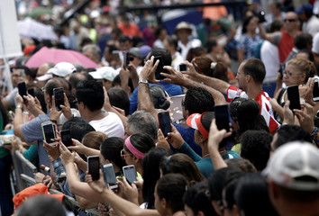 People use their cell phones to take pictures of the image of the Virgin of Los Angeles during a celebration of the Virgin of Los Angeles in Cartago