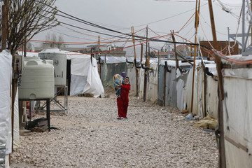 A Syrian refugee woman carries a child under pipes and wires near tents in an informal Syrian refugee camp in the Bekaa valley