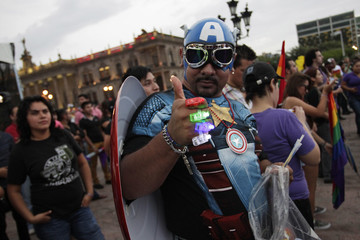 A participant dressed in a Captain America costume poses for a picture during the annual gay pride parade in Monterrey
