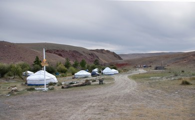 Mongolian national camp with white yurts in a desert river valley in dry steppe with red rocks under a cloudy sky Altai Mountains, Siberia, Russia