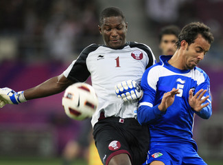 Qatar's goalkeeper Burhan and Kuwait's Ajab fight for the ball during their Asian Cup soccer match in Doha