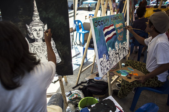 Artists paint images of Thai icons and the national flag of Thailand during a rally at the Democracy Monument in central Bangkok