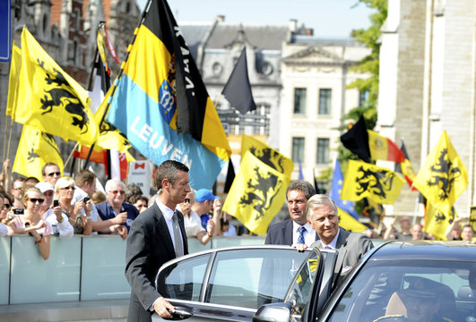 Belgium's King Philippe leaves his Joyous Entry as protesters who oppose royalty are seen in the background in Leuven