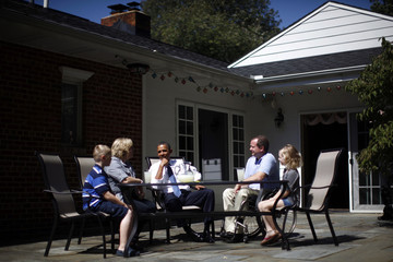 U.S. President Barack Obama speaks to John Nicholas and Nicole Armstrong and their children Trevor and Olivia at their house in Fairfax, Virginia