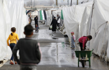 Syrian refugees walk next to their tents at the Boynuyogun refugee camp on the Turkish-Syrian border in Hatay province